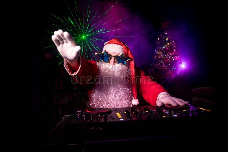DJ Santa Claus no Natal com vidros e na mistura da neve no evento da véspera de Ano Novo nos raios de luz fotografia de stock