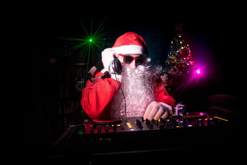 DJ Santa Claus no Natal com vidros e na mistura da neve no evento da véspera de Ano Novo nos raios de luz imagem de stock royalty free