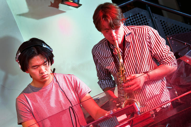 DJ and Saxophonist. Jamming together in a Dee Jay booth at a nightclub stock images