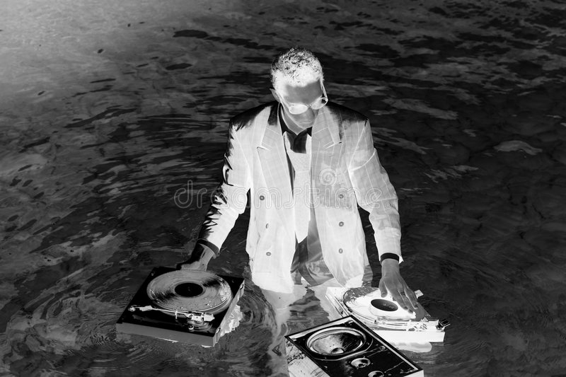 Dj in sea. A young dj plays music in the sea stock photography