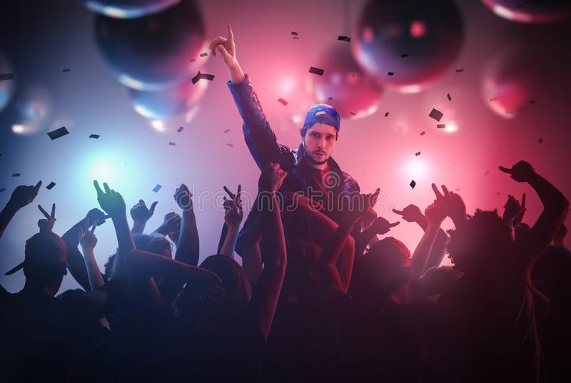 DJ or singer has hand up at disco party in club with crowd of people stock photos