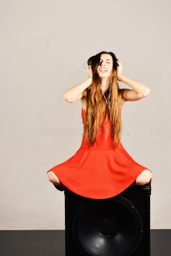 Dj sits on black boombox on light grey background. Girl with loose hair wears headphones. Music and party concept. stock images