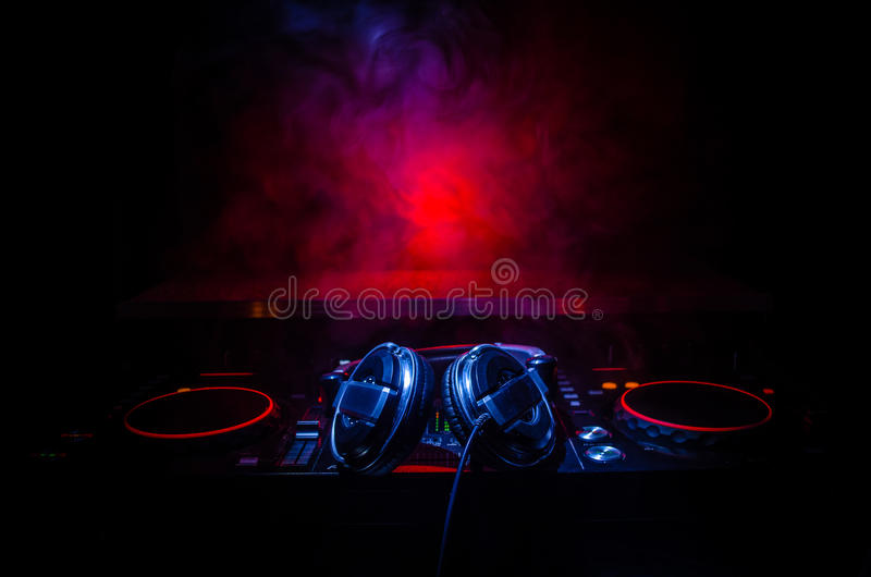 DJ Spinning, Mixing, and Scratching in a Night Club, Hands of dj tweak various track controls on dj's deck, strobe lights and fog,. Selective focus, close up stock image