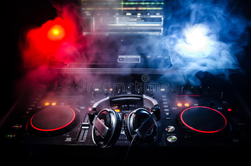DJ Spinning, Mixing, and Scratching in a Night Club, Hands of dj tweak various track controls on dj's deck, strobe lights and fog,. Selective focus, close up royalty free stock photos