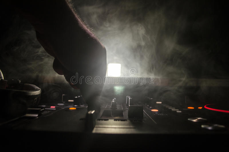 DJ Spinning, Mixing, and Scratching in a Night Club, Hands of dj tweak various track controls on dj's deck, strobe lights and fog,. Selective focus, close up stock photo