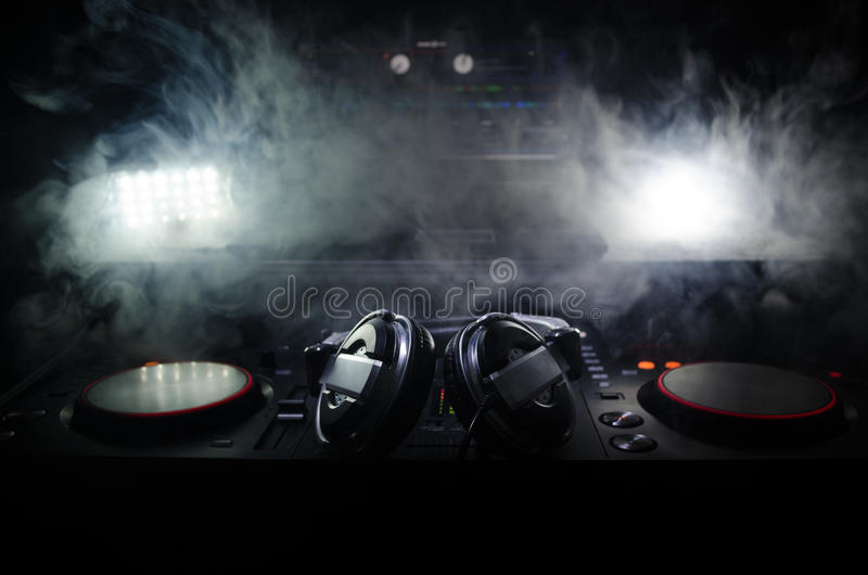 DJ Spinning, Mixing, and Scratching in a Night Club, Hands of dj tweak various track controls on dj's deck, strobe lights and fog,. Selective focus, close up royalty free stock images