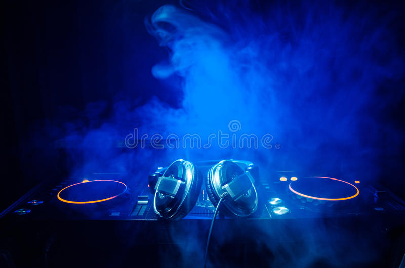 DJ Spinning, Mixing, and Scratching in a Night Club, Hands of dj tweak various track controls on dj's deck, strobe lights and fog,. Selective focus, close up stock photography