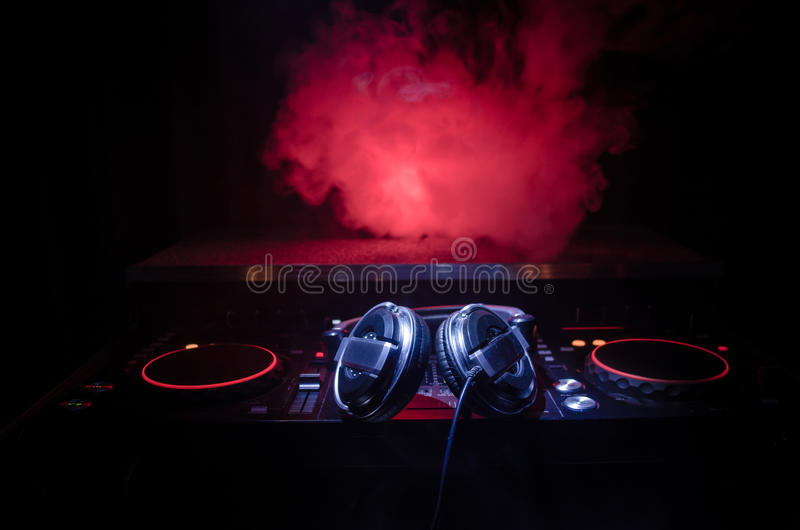 DJ Spinning, Mixing, and Scratching in a Night Club, Hands of dj tweak various track controls on dj's deck, strobe lights and fog,. Selective focus, close up royalty free stock photography