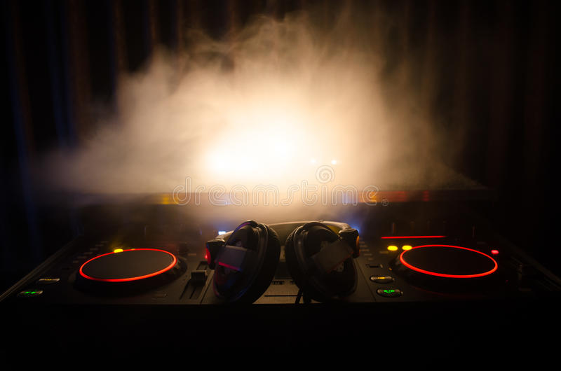 DJ Spinning, Mixing, and Scratching in a Night Club, Hands of dj tweak various track controls on dj's deck, strobe lights and fog,. Selective focus, close up stock photos