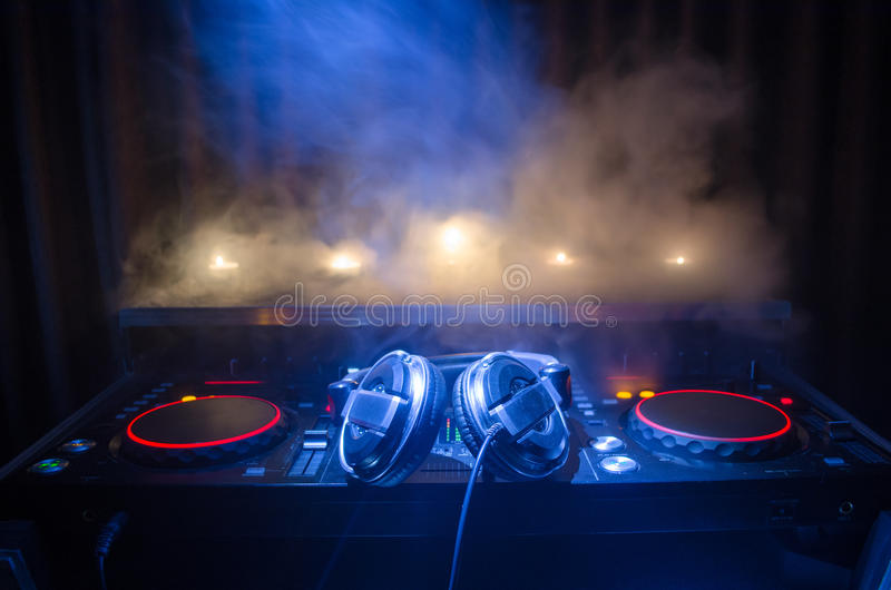 DJ Spinning, Mixing, and Scratching in a Night Club, Hands of dj tweak various track controls on dj's deck, strobe lights and fog,. Selective focus, close up royalty free stock image