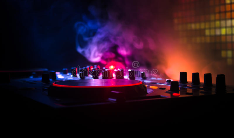 DJ Spinning, Mixing, and Scratching in a Night Club, Hands of dj tweak various track controls on dj's deck, strobe lights and fog. Selective focus, close up stock image