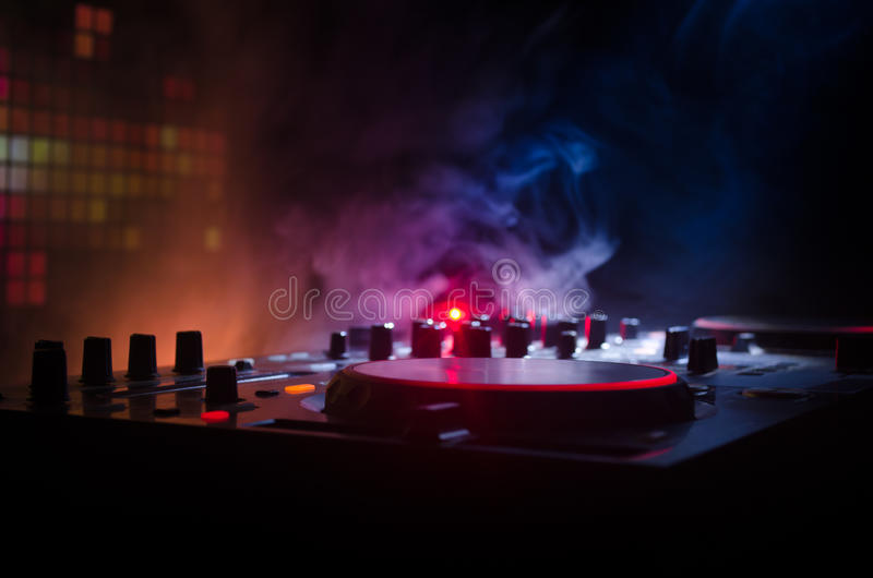 DJ Spinning, Mixing, and Scratching in a Night Club, Hands of dj tweak various track controls on dj's deck, strobe lights and fog. Selective focus, close up stock photo