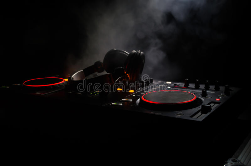 DJ Spinning, Mixing, and Scratching in a Night Club, Hands of dj tweak various track controls on dj's deck, strobe lights and fog. Selective focus, close up royalty free stock photography