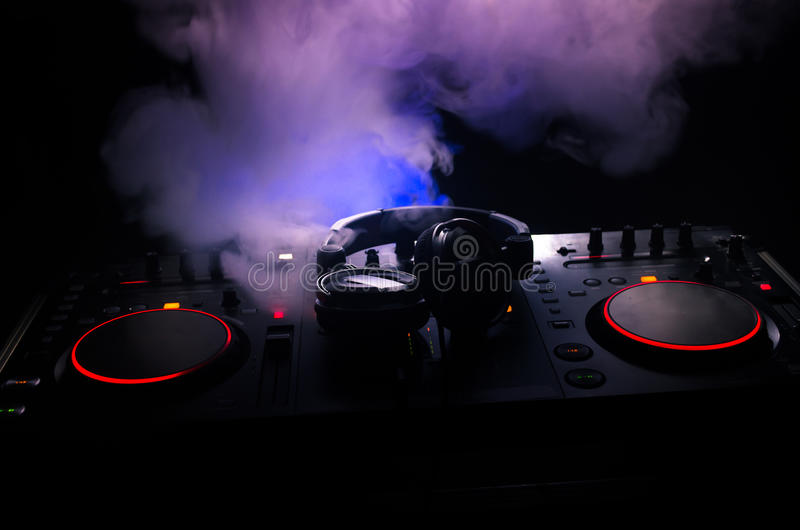 DJ Spinning, Mixing, and Scratching in a Night Club, Hands of dj tweak various track controls on dj's deck, strobe lights and fog. Selective focus, close up stock photos