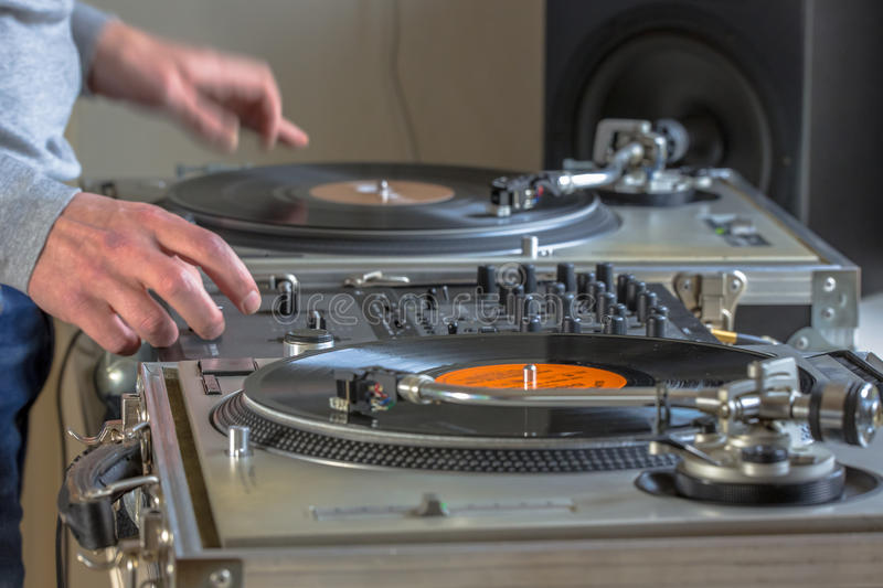 DJ studio at home. Hands of DJ playing music from vinyl records in his home studio stock photography