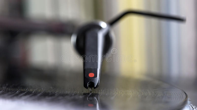 Dj stylus on spinning vinyl, record background. Dj needle stylus on spinning record, vinyl background stock photography