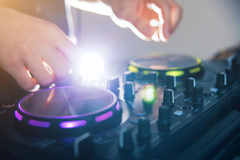 DJ turntable console mixer controlling. With two hand in concert nightclub stage stock photo
