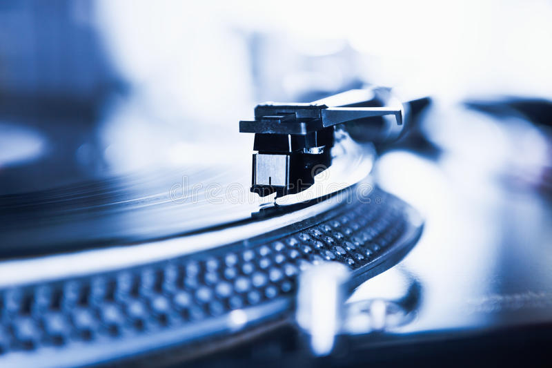 Dj turntable vinyl record player close up. Turntable vinyl records player playing analog record disc with music.Close up,focus on needle cartridge headshell.DJ stock image