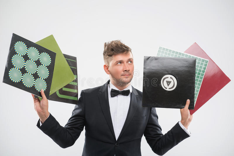 DJ in tuxedo showing his vinyl records standing by. Half-length portrait of stylish handsome DJ in tuxedo showing his colorful vinyl records isolated on white stock image