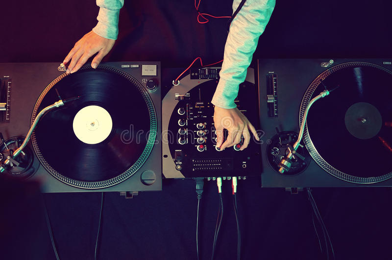 Dj using equipment. Dj hands on equipment deck and mixer with vinyl record at party stock photography