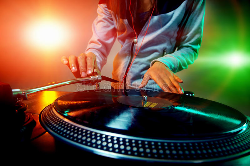 Dj using equipment. Dj hands on equipment deck and mixer with vinyl record at party royalty free stock photo