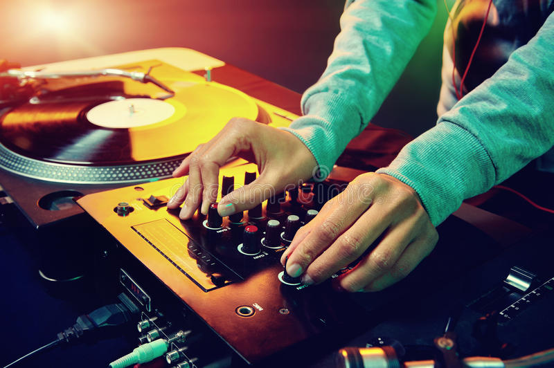 Dj using equipment. Dj hands on equipment deck and mixer with vinyl record at party royalty free stock images