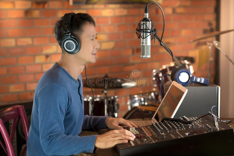 DJ working at radio broadcasting studio,hands adjusting volume. NMale radio broadcaster using laptop computer and audio mixer controlling his live radio program royalty free stock photos