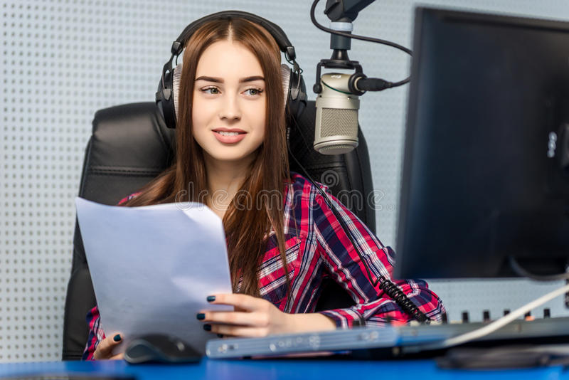 Dj working on the radio. Female dj working in front of a microphone on the radio stock photography
