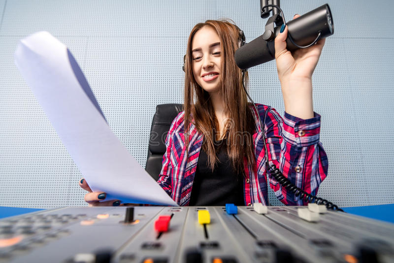 Dj working on the radio. Female dj working in front of a microphone on the radio royalty free stock image