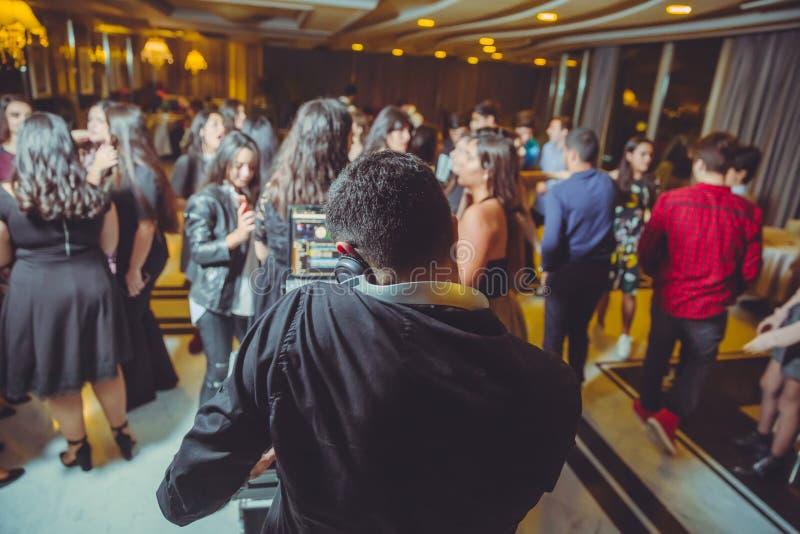 DJ z hełmofonami przy noc klubem bawi się pod kolorowym światłem i ludzie tłoczą się w tle Dj przy otwartym Aire bawi się Nocy pr zdjęcie stock