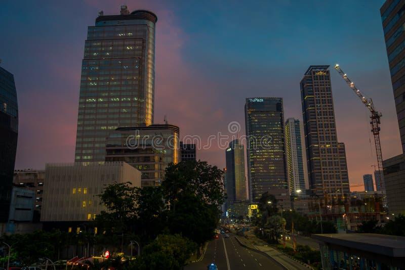 DJAKARTA, INDONESIË - 3 MAART, 2017: Modern deel van stadshorizon zoals die van afstand, mooie zonsonderganghemel met purple word royalty-vrije stock afbeelding