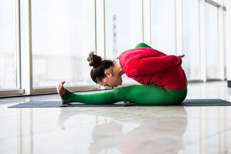 Djanu-shirasana. Beautiful yoga woman practice in a big window. Hall background. Yoga concept stock image