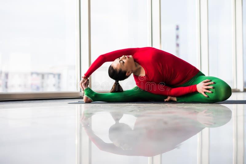Djanu-shirasana. Beautiful yoga woman practice in a big window. Hall background. Yoga concept royalty free stock photo