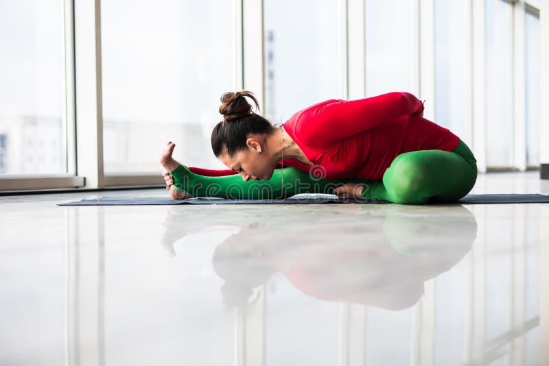 Djanu-shirasana. Beautiful yoga woman practice in a big window hall background. Yoga concept stock photography