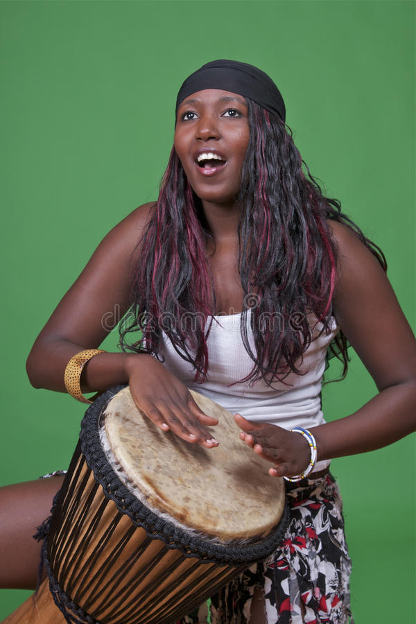 Djembe drummer on green. A female djembe drummer is isolated on a green background for easy extraction, or to be used as is stock photos