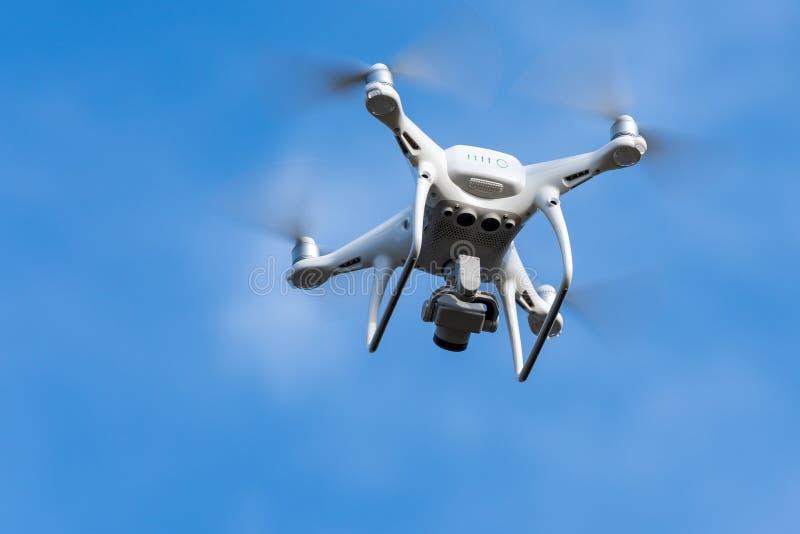 DJI Phantom 4 Pro — dron czterokołowca z cyfrowym aparatem 4K, latający na niebieskim niebie, robi zdjęcia z lotu ptaka zdjęcie stock