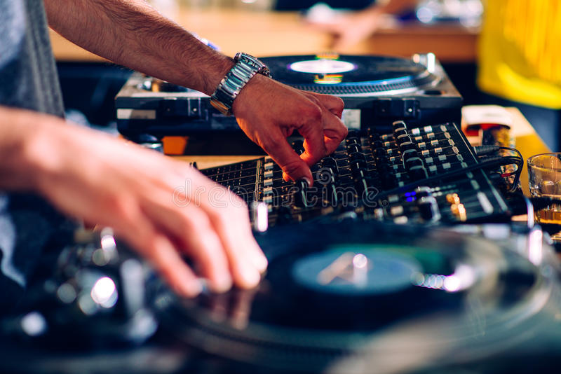 DJs hands on turntable. Selective focus stock images
