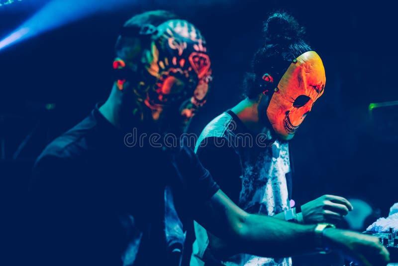 Djs que sorprende con la máscara que juega música de mezcla en el verano va de fiesta festival fotos de archivo libres de regalías