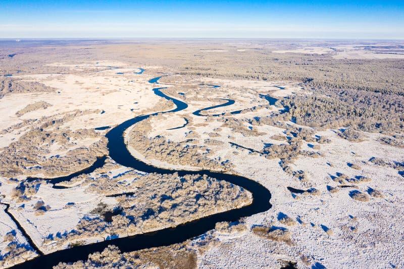 Djup flod som buktar runt om snöig fält och skogen, flyg- sikt arkivfoto