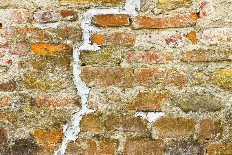 Djup grouted spricka i gammal tegelstenvägg - begreppsbild med kopia s fotografering för bildbyråer
