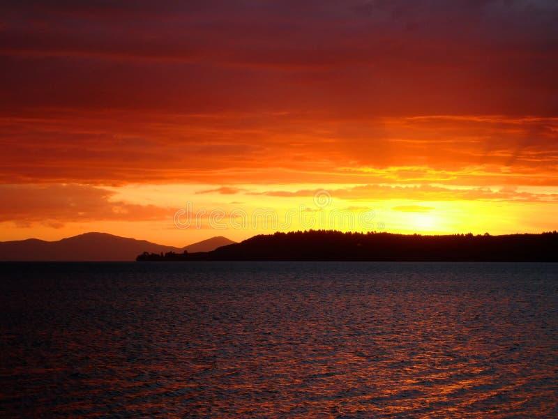 djup lake som är ny över den röda solnedgångtaupoen zealand arkivfoton
