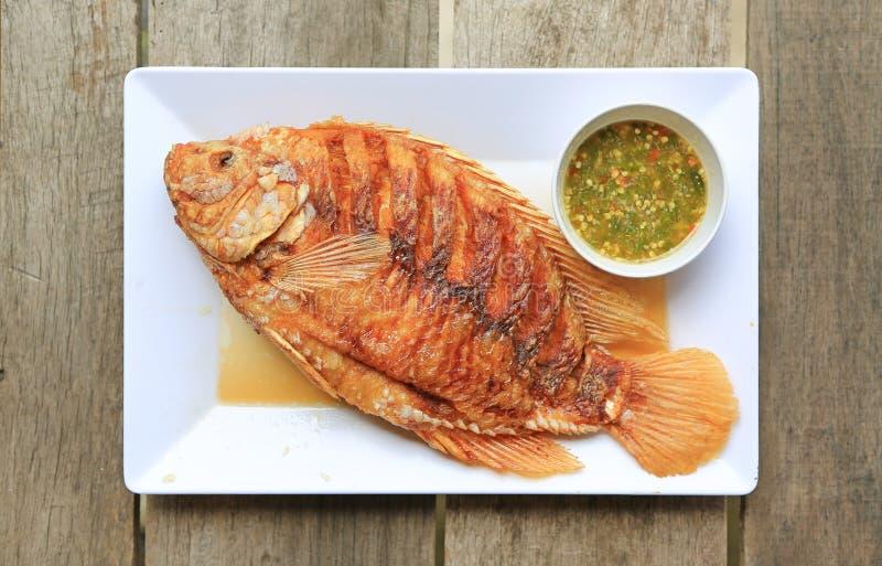 Djup stekt rubinfisk på den vita fyrkantiga plattan med kryddig sås mot trätabellen - berömd thailändsk matmeny royaltyfria foton