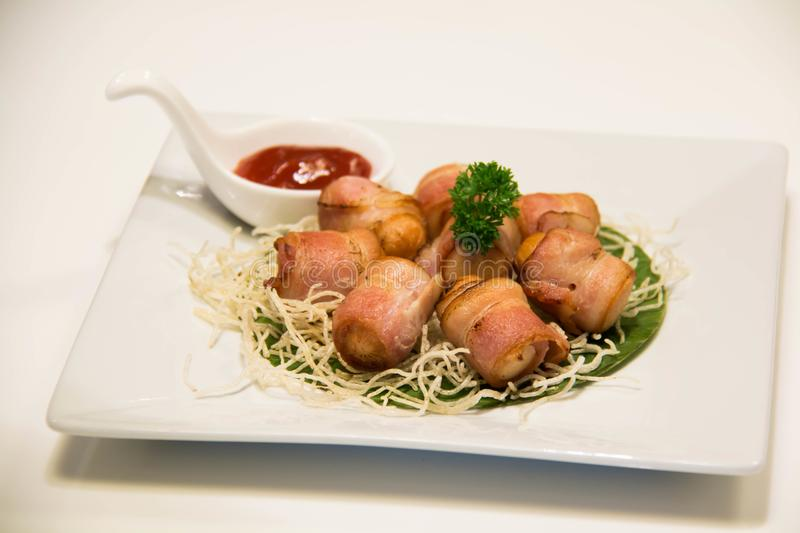 Djupa Fried Bacon Wrapped Sausage med sås royaltyfri foto