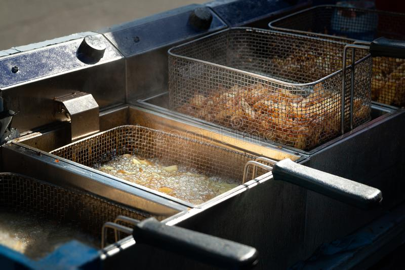 djupa stekte potatisar Pommes frites som stekas, i att koka olja i en stekpanna fotografering för bildbyråer