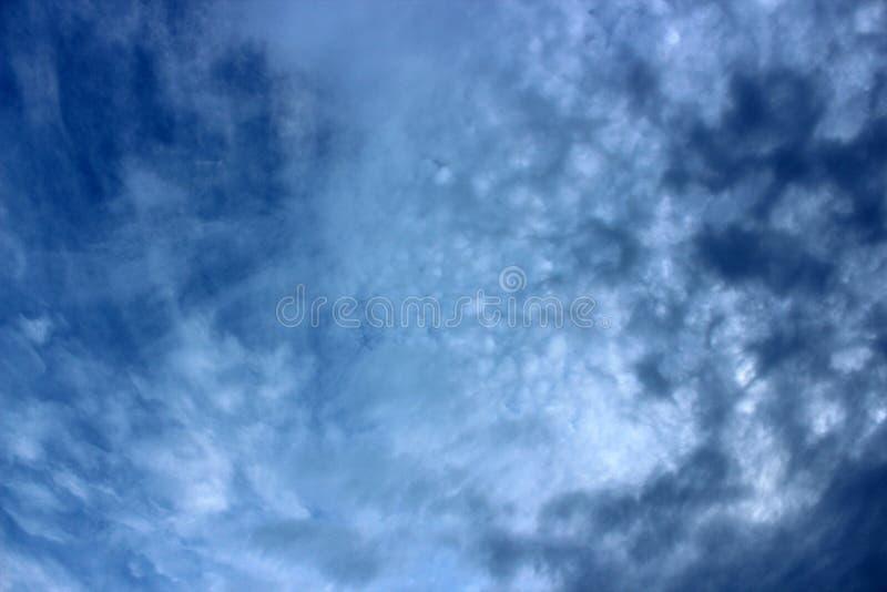 Djupblå lynniga himlar med mörkare blåa och vita virvlar av molnet som flyttar sig över yttersidan arkivbilder