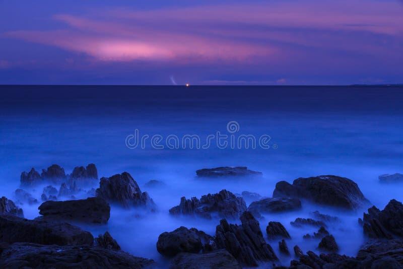 Djupblått hav på skymning med avlägsna exponeringar av blixt arkivbild