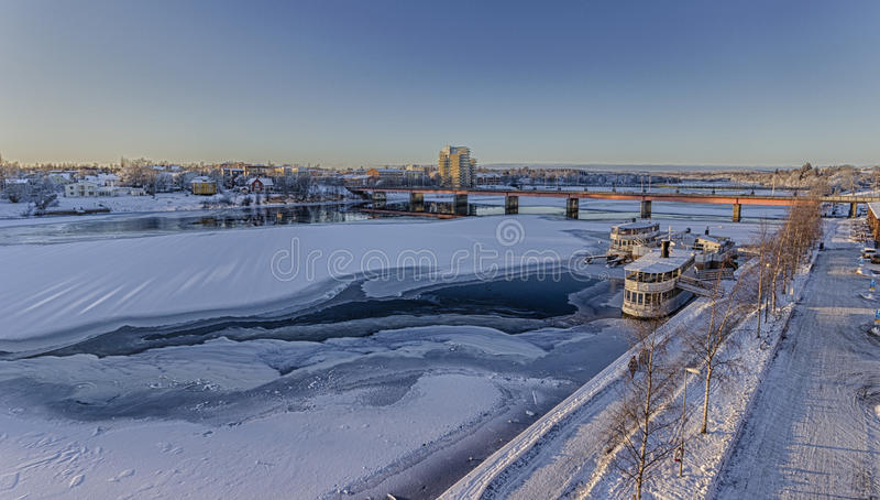 Djupfryst flod med Brigde i Umeå, Sverige royaltyfria bilder