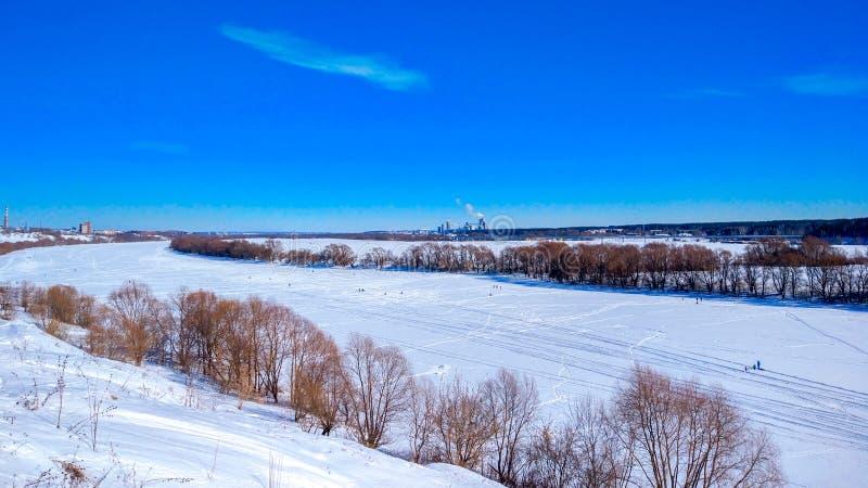 Djupfryst flodvinter som täckas med snö Härligt sjölandskap i is Klar blå himmel med moln royaltyfri fotografi