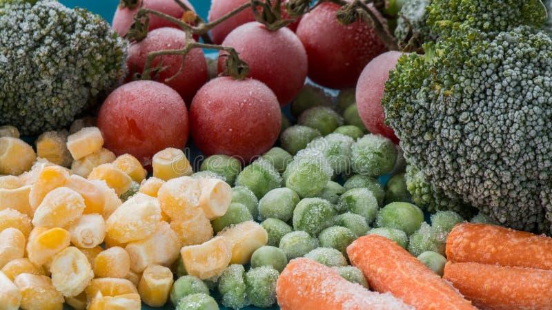 Djupfryst grönsakbroccoli, körsbärsröda tomater, havre, ärta, morot arkivbild