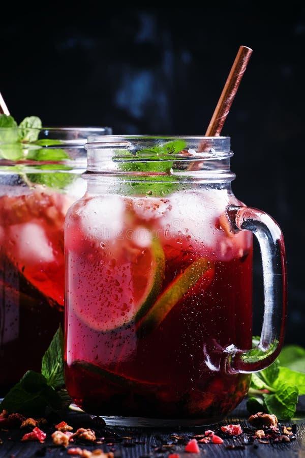 Djupfryst rött te med limefrukt, is och mintkaramellen i glass krus, mörk backg arkivfoton